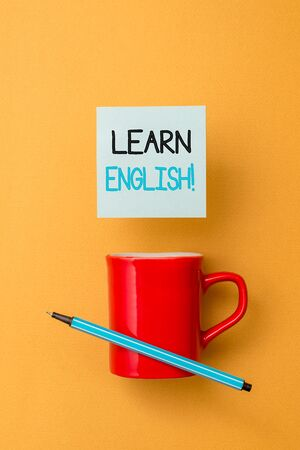 Writing note showing Learn English. Business concept for gain acquire knowledge in new language by study Front view coffee cup colored sticky note pen yolk color background Foto de archivo