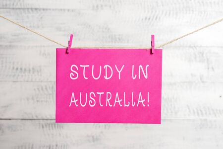 Word writing text Study In Australia. Business photo showcasing going into foreign country order complete your studies Clothesline clothespin rectangle shaped paper reminder white wood desk