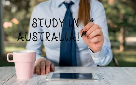 Writing note showing Study In Australia. Business concept for going into foreign country order complete your studies Female business person sitting by table and holding mobile phone