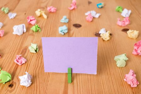 Colored crumpled papers empty reminder wooden floor background clothespin