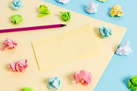 Colored crumpled papers empty reminder blue yellow background clothespin