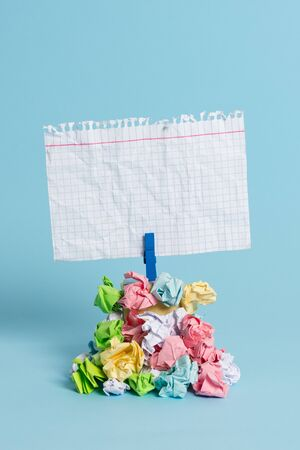 Reminder pile colored crumpled paper clothespin reminder blue background