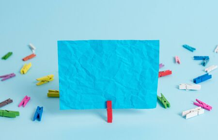 Colored clothespin rectangle square shaped paper light blue background
