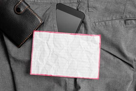 Smartphone device inside trousers front pocket with wallet and note paper Stockfoto