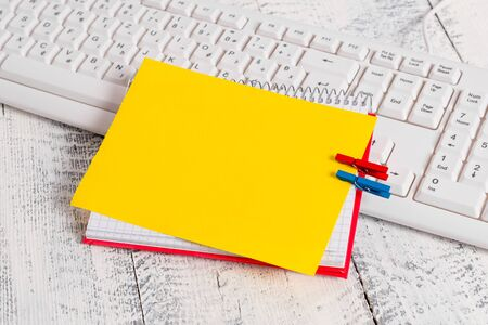 Notebook paper reminder clothespin pinned sheet white keyboard light wooden