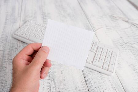 Man holding colorful reminder square-shaped paper white keyboard wood floor Stock fotó