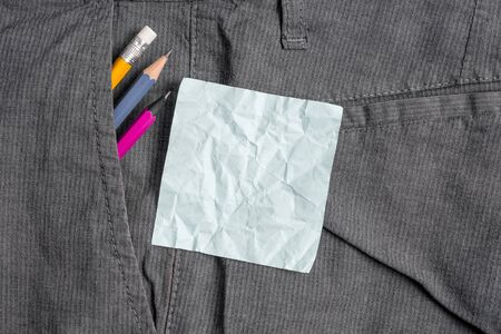 Writing equipment and blue note paper inside pocket of man work trousers Фото со стока