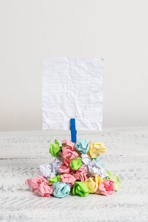 Reminder pile colored crumpled paper clothespin reminder white wooden space 写真素材
