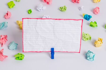 Colored crumpled papers empty reminder white floor background clothespin