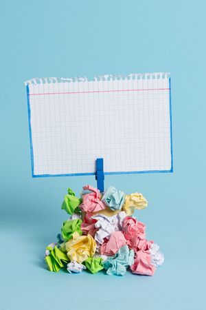 Reminder pile colored crumpled paper clothespin reminder blue background 写真素材