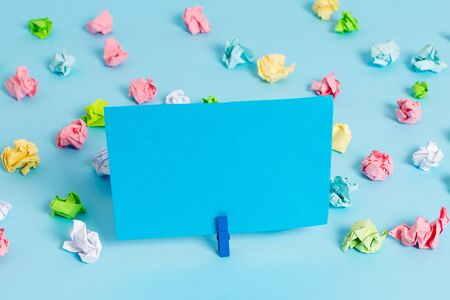 Colored crumpled papers empty reminder blue floor background clothespin