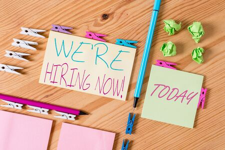 Handwriting text writing We Re Hiring Now. Conceptual photo recently employ someone or pay someone to do particular job Colored clothespin papers empty reminder wooden floor background office