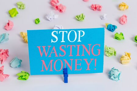 Writing note showing Stop Wasting Money. Business concept for advicing demonstrating or group to start saving and use it wisely Colored crumpled paper empty reminder white floor clothespin Stockfoto