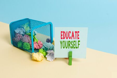 Text sign showing Educate Yourself. Business photo showcasing prepare oneself or someone in a particular area or subject Trash bin crumpled paper clothespin empty reminder office supplies tipped