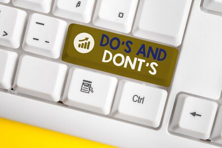 Conceptual handwriting showing Do's And Don'ts. Concept meaning Rules or customs concerning some activity or actions White pc keyboard with note paper above the white background Foto de archivo - 128685688