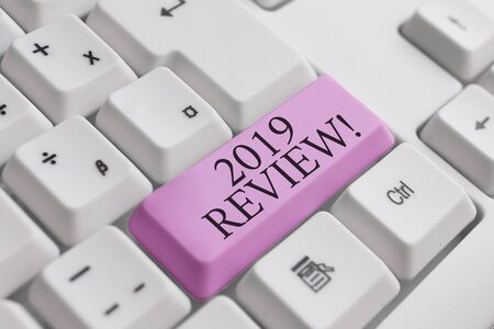 Conceptual hand writing showing 2019 Review. Concept meaning remembering past year events main actions or good shows White pc keyboard with note paper above the white background