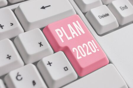 Conceptual hand writing showing Plan 2020. Concept meaning detailed proposal doing achieving something next year White pc keyboard with note paper above the white background