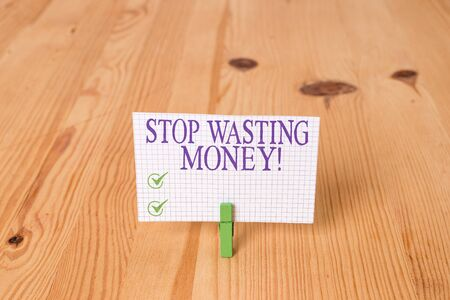 Writing note showing Stop Wasting Money. Business concept for advicing demonstrating or group to start saving and use it wisely Wooden floor background green clothespin groove slot office Stockfoto