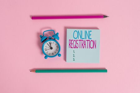 Handwriting text Online Registration. Conceptual photo System for subscribing or registering via the Internet Metal vintage alarm clock wakeup blank notepad markers colored background