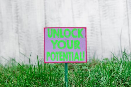 Text sign showing Unlock Your Potential. Business photo text release possibilities Education and good training is key Plain empty paper attached to a stick and placed in the green grassy land Banco de Imagens