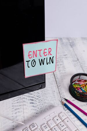 Word writing text Enter To Win. Business photo showcasing exchanging something value for prize or chance of winning Note paper taped to black computer screen near keyboard and stationary