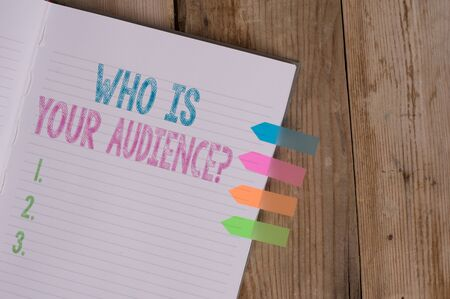 Text sign showing Who Is Your Audience Question. Business photo text who is watching or listening to it Striped note book four colored arrow banners reminder wooden background