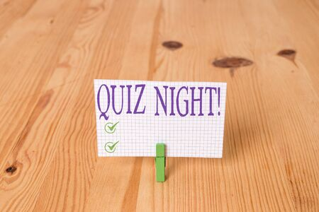 Writing note showing Quiz Night. Business concept for evening test knowledge competition between individuals Wooden floor background green clothespin groove slot office Imagens