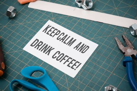 Writing note showing Keep Calm And Drink Coffee. Business concept for encourage demonstrating to enjoy caffeine drink and relax Stationary and carpentry tools with paper above a textured backdrop