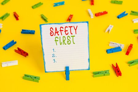 Handwriting text Safety First. Conceptual photo used to say that the most important thing is to be safe Colored clothespin papers empty reminder yellow floor background office