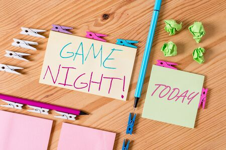 Handwriting text writing Game Night. Conceptual photo usually its called on adult play dates like poker with friends Colored clothespin papers empty reminder wooden floor background office