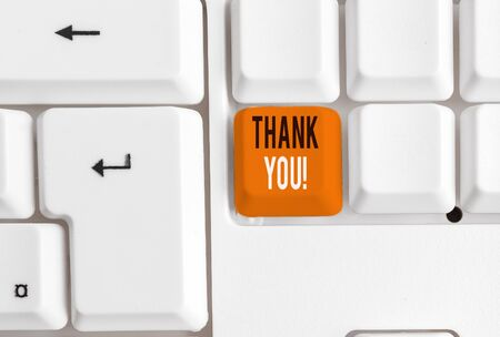 Writing note showing Thank You. Business concept for polite expression used when acknowledging gift service compliment White pc keyboard with note paper above the white background