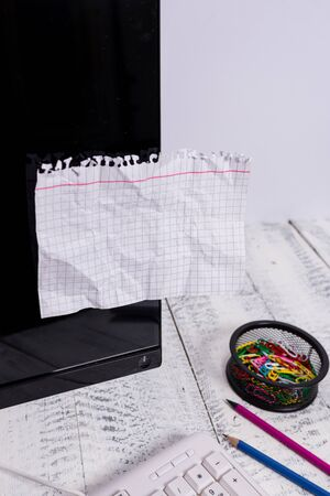 Note paper taped to black computer screen near keyboard and stationary Stockfoto