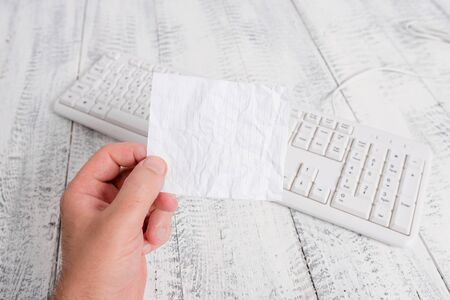 man holding colorful reminder square shaped paper white keyboard wood floor Stockfoto