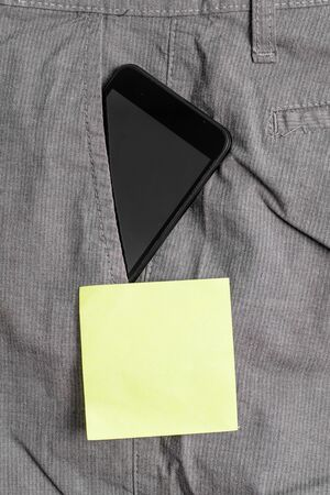 Smartphone device inside formal work trousers front pocket near note paper