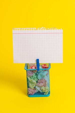 Trash bin crumpled paper clothespin empty reminder office supplies yellow Stockfoto