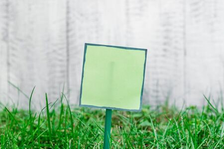 Plain empty paper attached to a stick and placed in the green grassy land Stockfoto