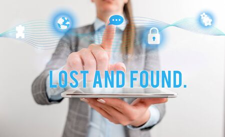Conceptual hand writing showing Lost And Found. Concept meaning a place where lost items are stored until they reclaimed Female human wear formal work suit presenting smart device