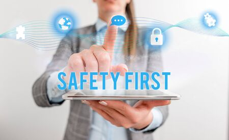 Conceptual hand writing showing Safety First. Concept meaning used to say that the most important thing is to be safe Female human wear formal work suit presenting smart device