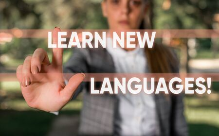 Word writing text Learn New Languages. Business photo showcasing developing ability to communicate in foreign lang Business woman in the nature pointing with the finger into empty space Stock Photo