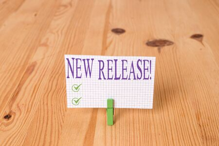 Writing note showing New Release. Business concept for announcing something newsworthy recent product Wooden floor background green clothespin groove slot office
