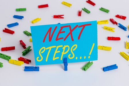 Text sign showing Next Steps. Business photo text something you do after you have finished doing first one Colored clothespin papers empty reminder white floor background office Imagens