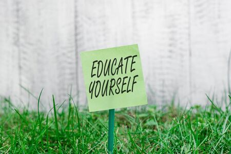 Word writing text Educate Yourself. Business photo showcasing prepare oneself or someone in a particular area or subject Plain empty paper attached to a stick and placed in the green grassy land