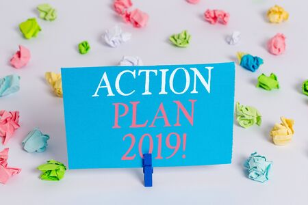 Writing note showing Action Plan 2019. Business concept for proposed strategy or course of actions for current year Colored crumpled paper empty reminder white floor clothespin Banque d'images