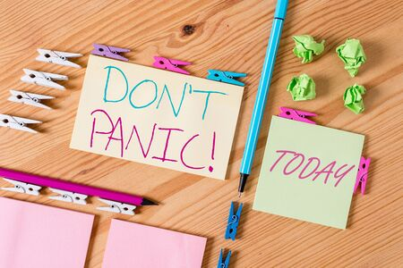 Handwriting text writing Don't Panic. Conceptual photo suddenly feel so worried or frightened that you can not behave Colored clothespin papers empty reminder wooden floor background office