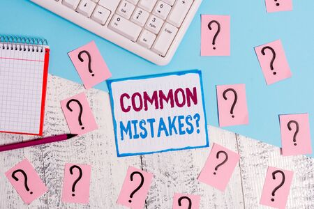 Writing note showing Common Mistakes Question. Business concept for repeat act or judgement misguided making something wrong Writing tools and scribbled paper on top of the wooden table