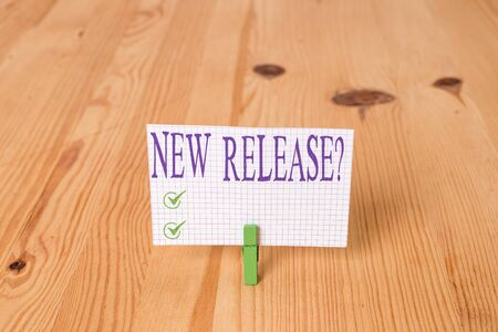 Writing note showing New Release Question. Business concept for asking about recent product or service newly unleashed Wooden floor background green clothespin groove slot office 스톡 콘텐츠