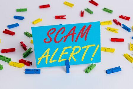 Signe texte montrant Scam Alert. Texte photo d'affaires obtenir frauduleusement de l'argent de la victime en le persuadant de papiers pince à linge de couleur rappel vide bureau fond blanc