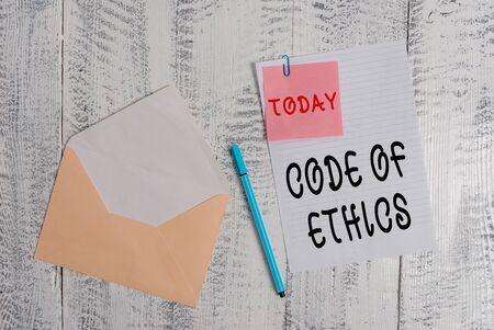 Pisanie notki przedstawiającej Kodeks Etyki. Koncepcja biznesowa dla podstawowego przewodnika dla profesjonalnego postępowania i nakłada obowiązki Koperta pusty arkusz karteczkę samoprzylepną długopis drewniane tło Zdjęcie Seryjne