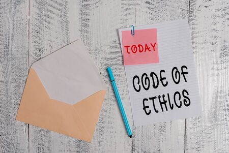 Writing note showing Code Of Ethics. Business concept for basic guide for professional conduct and imposes duties Envelope blank sheet sticky note ballpoint wooden background