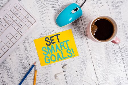 Conceptual hand writing showing Set Smart Goals. Concept meaning list to clarify your ideas focus efforts use time wisely Technological devices colored reminder paper office supplies Banco de Imagens